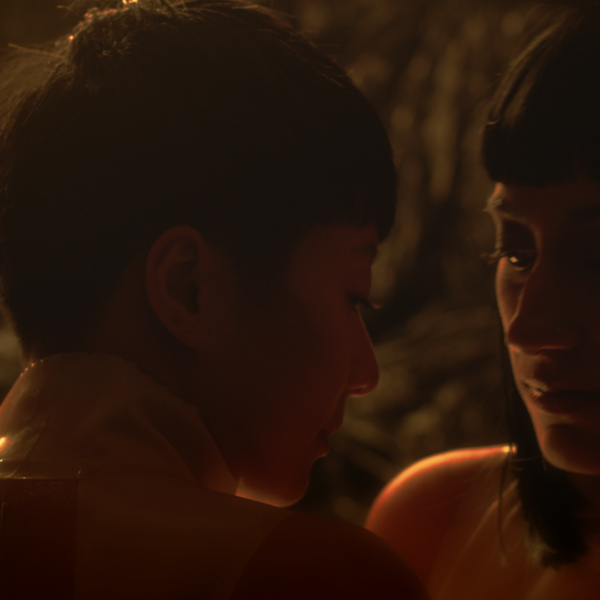A close up of two femme-presenting persons leaning into each other in a dark enclosure.
