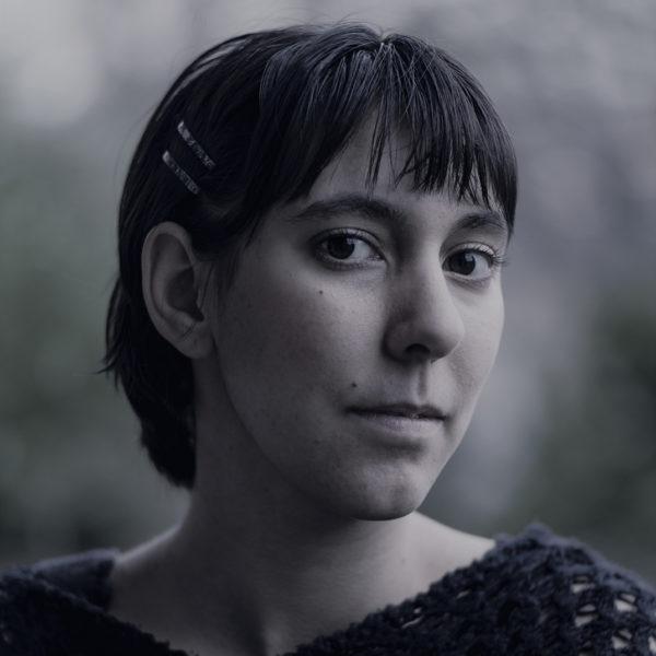 A headshot of artist Danielle Mackenzie standing outside.