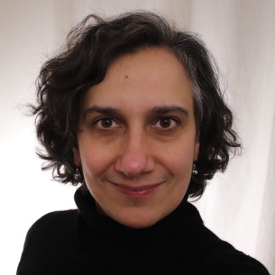 A headshot of artist Juli Saragosa standing in front of a white textile.