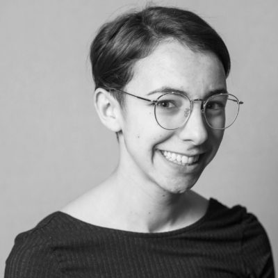 A black and white photo of artist Mallory Donen smiling widely.