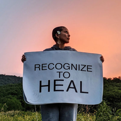 """Artist Gina Goico spreads her arms holding a poster that reads, """"Recognize to heal"""", in front of a hill against a pastel-coloured sky."""