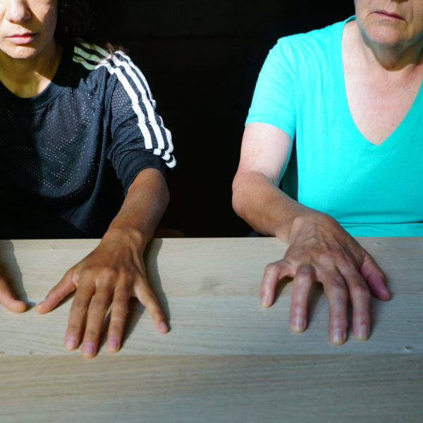 Two individuals sit side by side with both of their hands spread out on a table.