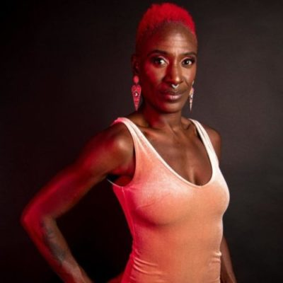 Artist Natasha Courage Bacchus stands straight against a black backdrop in a studio setting.