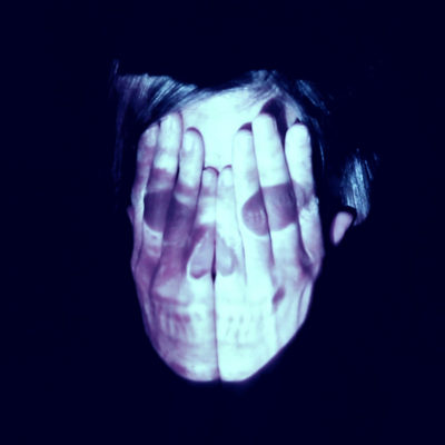 A person covering their face with both hands while and image of a skull projects on top.