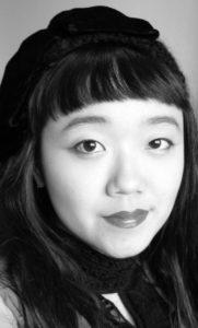 A black and white headshot photo of Minah Lee. She has long dark hair and bangs.